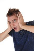 Screaming young man with hands on his ears