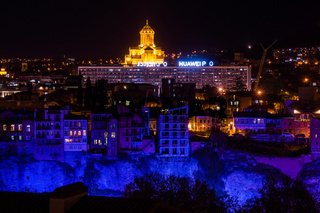 blue and yellow illuminated cathedral and houses