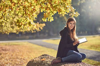 Pretty young woman relaxing in an autumn park