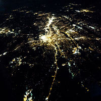 Flying at night over cities below
