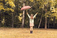 Child girl with umbrella stands at park