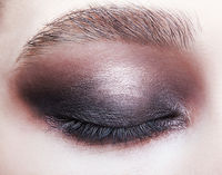 Closeup macro portrait of closed human female eye.  Girl with perfect violet - black smoky eyes make-up.