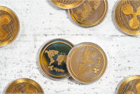 Top down view, XRP ripple cryptocurrency golden coins on white stone like board