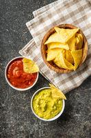 Corn nacho chips with avocado and tomato dip. Yellow tortilla chips and guacamole salsa.