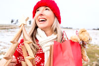 Joyous woman holding small wooden Christmas tree and gift bags