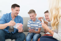 Happy young family playing card game at home.