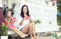 Young family eating a juicy red watermelon