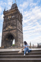 Woman with a dog in front of the tower of Charles Bridge