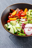 Vegan buddha bowl. Healthy vegetarian salad with cherry tomatoes, cucumber, radish,, avocado and lettuce.