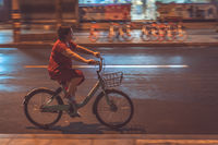 Chinese woman on a bicycle at night