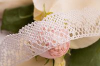 White lace ribbon on the table among roses shot