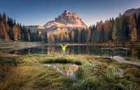Man with raised up arms on Antorno lake in autumn at sunrise