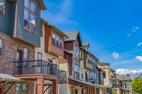 Bright sunlight beaming down on the row of houses with small balconies