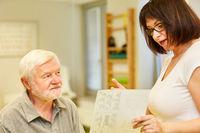 Heilpraktikerin erklärt Senior Patient den Therapieplan