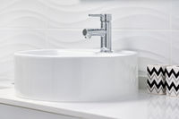 Close up of new clean white round shaped ceramic sink and faucet on tiled wall background, two storages for toothbrushes and toothpaste tubes in the modern cozy bathroom, no people