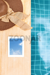 Sunhat and Tablet near blue swimming pool from above.