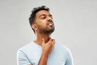 indian man suffering from neck pain or sore throat