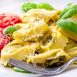 ravioli with spinach filling, grated cheese and cocktail tomatoes
