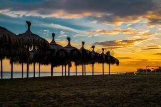Straw beach umbrellas at sunset