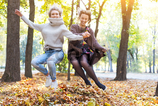 Fashionable beautiful young girlfriends walking together in the autumn park background. Having fun and posing.