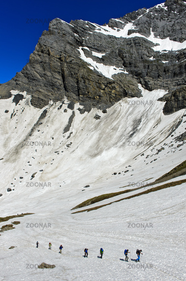 Alpinists crossing a snowfield in the Plan Salentse cirque on the way to the Rambert Hut,Valais