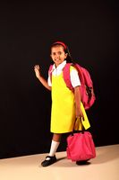 Little girl in school uniform posing in front of camera. Pune, Maharashtra