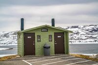 Unisex public restroom against lake snowy mountain and cloudy sky in winter