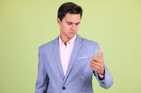 Portrait of young handsome businessman using phone