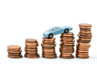 Mini car model on stack of coins