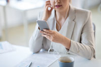 businesswoman with earphones and smartphone