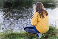 Girl sitting on the edge of the river.