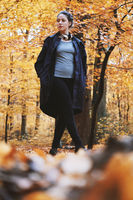 young woman enjoying autumn walk in the woods