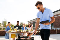 man cooking meat on bbq at rooftop party