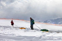 Father and daughter with snow tube in snowy sunlight mountains