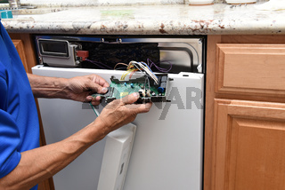 Closeup of a appliance repairman unplugging the control panel to a broken dishwasher