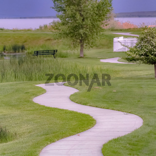 Square Pathway curving through grassy terrain with a pond and bench in the background