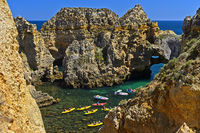 Kayakers in the rock formation at the Camilo beach, Praia do Camilo, Lagos, Algarve, Portugal