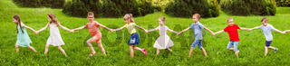 Kids walking on grass hill holding hands at sunny day