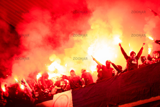 football hooligans with mask holding torches in fire
