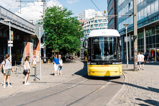 Yellow public transportation tram passing by the city of Berlin