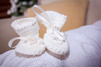 White booties for the baby. Knitted shoes for the baby. Beautiful socks