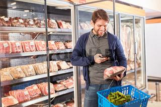 Mann scannt mit Smartphone App ein Fleisch Produkt