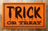 Trick Or Treat Halloween Orange Welcome Mat On Wood Floor Background