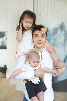 Portrait of a happy young father with a baby son and little daughter at home