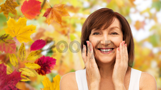 portrait of smiling senior woman touching her face