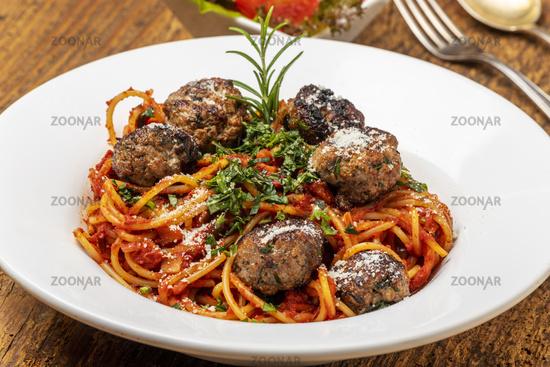 Spaghetti with meatballs on dark wood