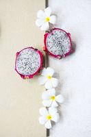 White frangipani and dragon fruit on light background