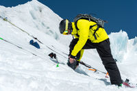 A professional skier standing on a glacier is preparing for a jump while setting up ski equipment. The concept of quality training for the sport