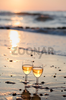 Two wine glasses with white wine standing on beach