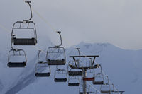 Chair lift and high snow mountains in fog at winter evening